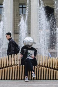 Person with glitter ball head reading a magazine called Ideas