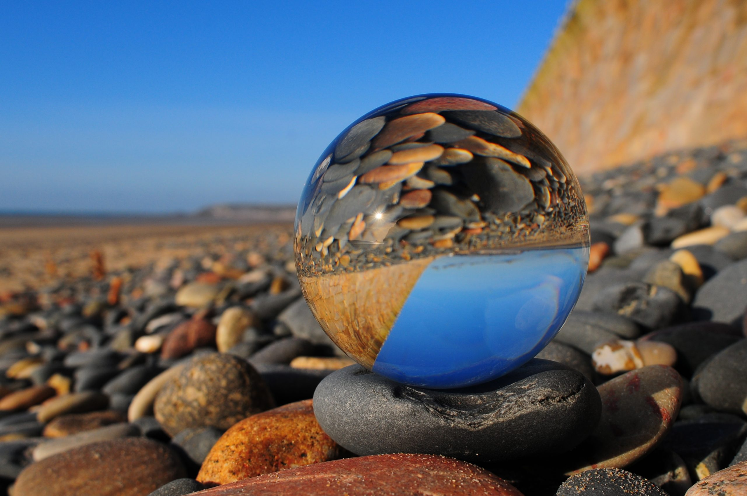 There is a ball on a pebble beach which is a metaphor for the different perspectives on domestic violence.