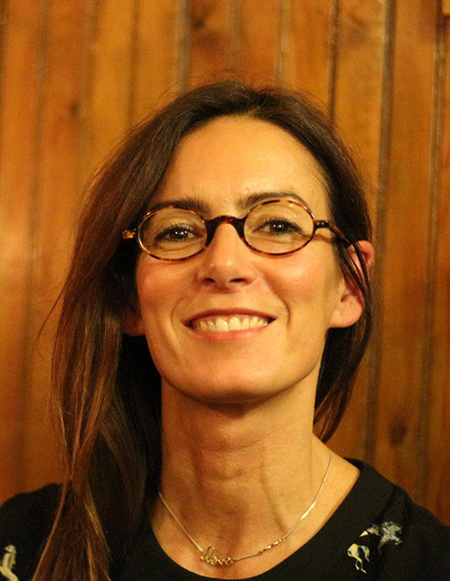 Isabel Casanova, a white woman with long dark hair and glasses smiling