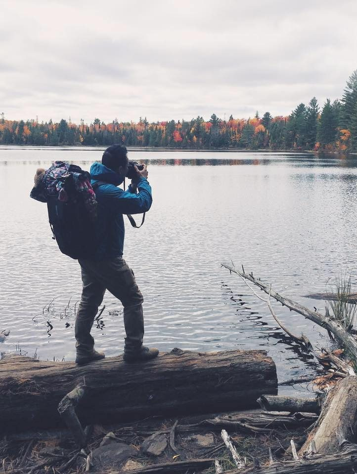 Taekyom Kim stands on a log beside a lake with a large backpack, taking a picture