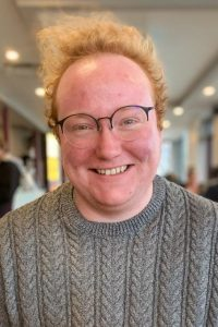 Caleb, a white man with curly red hair and large round glasses smiling.