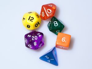 Six polyhedral dice: one blue d4, one orange d6, one green d8, one red d10, one yellow d12, and one purple d20