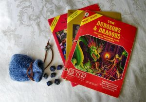 A fuzzy blue drawstring pouch lays on a table with dark blue polyhedral dice spilling out. A the 1981 Dugeons & Dragons rules booklet lays fanned out on top of two adventure module expansion booklets.
