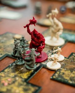A large red monster figurine has a weapon raised above his head. The monster is surrounded by 7 small figurines with bows, spears, and swords. The figurines are placed on map tiles which describe and map out the environment.